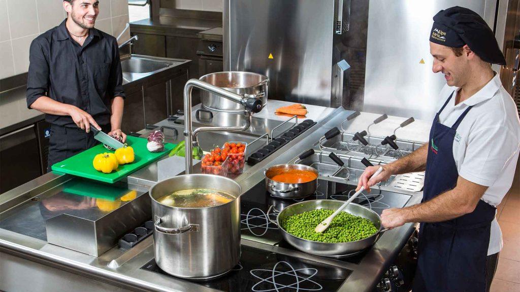 Chef cucinano su cucina professionale a induzione